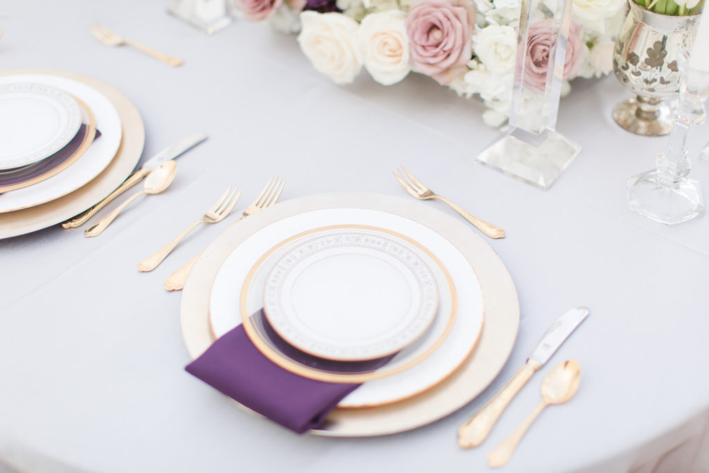 Silver satin linen, deep purple napkin tucked between the dinner plate and salad plate. Plates are bone white white trimmed in muted gold. This blend of colors creates a harmonious break in the design scheme so it doesn't look matchy matchy. It works together nicely